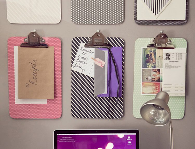 Decorative clipboards on the wall helps keep paper from piling up on your desk.