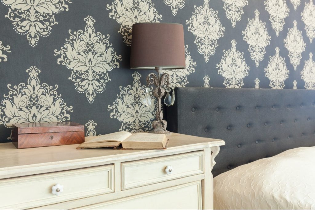 A bedroom with temporary patterned wallpaper on an accent wall is one way to decorate walls without paint.