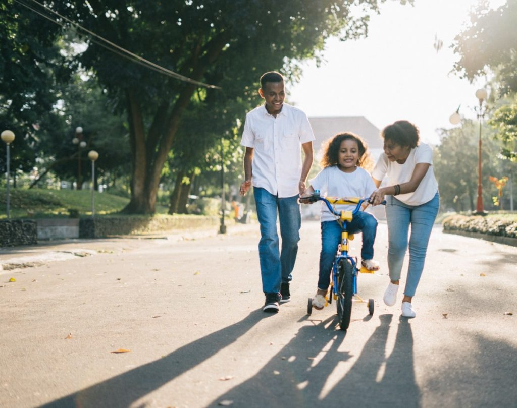Parents helping their daughter ride a bike.