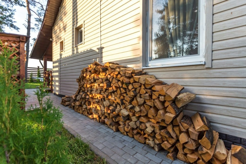Wood logs stacked on the side of a house.