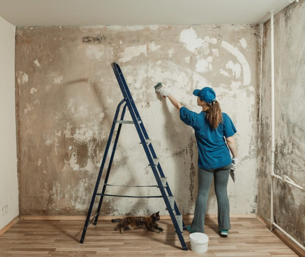 Women in blue applying plaster to a wall to fix cracks and holes in a room.