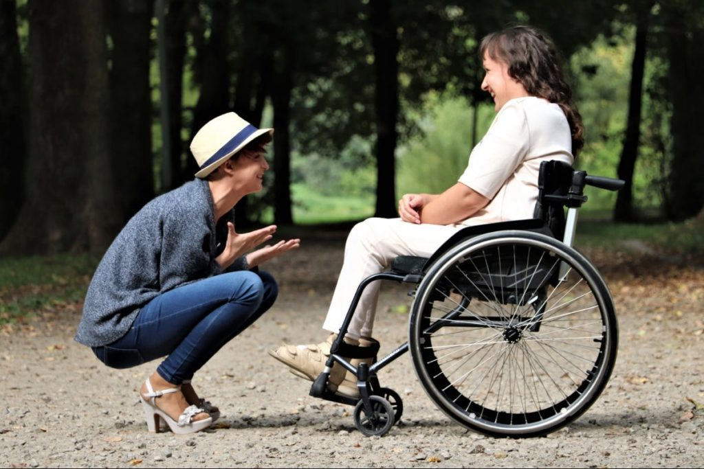 A woman talking to a disabled woman in a wheelchair.