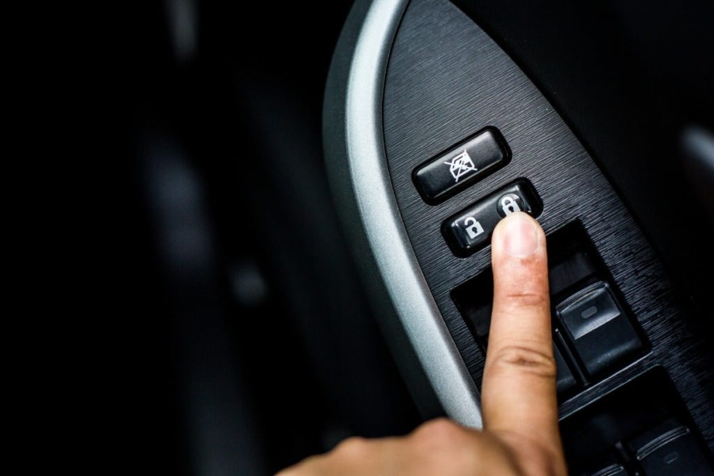 Pointer finger is pushing the window lock button on the driver's door panel.