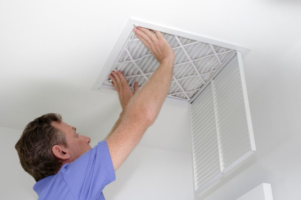 Man installing air filter in ceiling vent in an eco-friendly home.