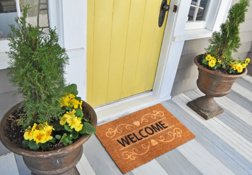"""Front door area. Brown floor mat that reads """"Welcome."""" Yellow front door. Two tall flower planters on each  side of door with yellow flowers and green shubbery."""