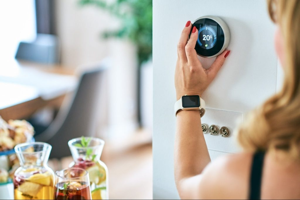 Women is adjusting the temperature using a digital thermostat in an eco-friendly home.
