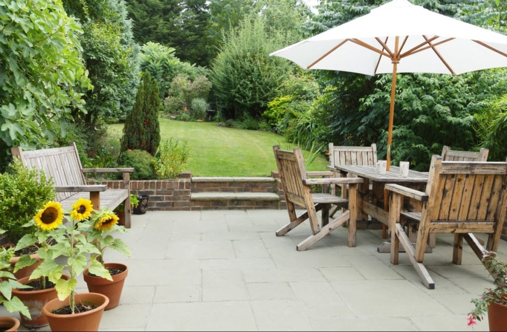 Backyard patio. Natural wood patio furniture set: table, chairs, umbrella and bench. Sunflowers and other greenery sitting in pots. Updated furniture is a great way to create rental home curb appeal.
