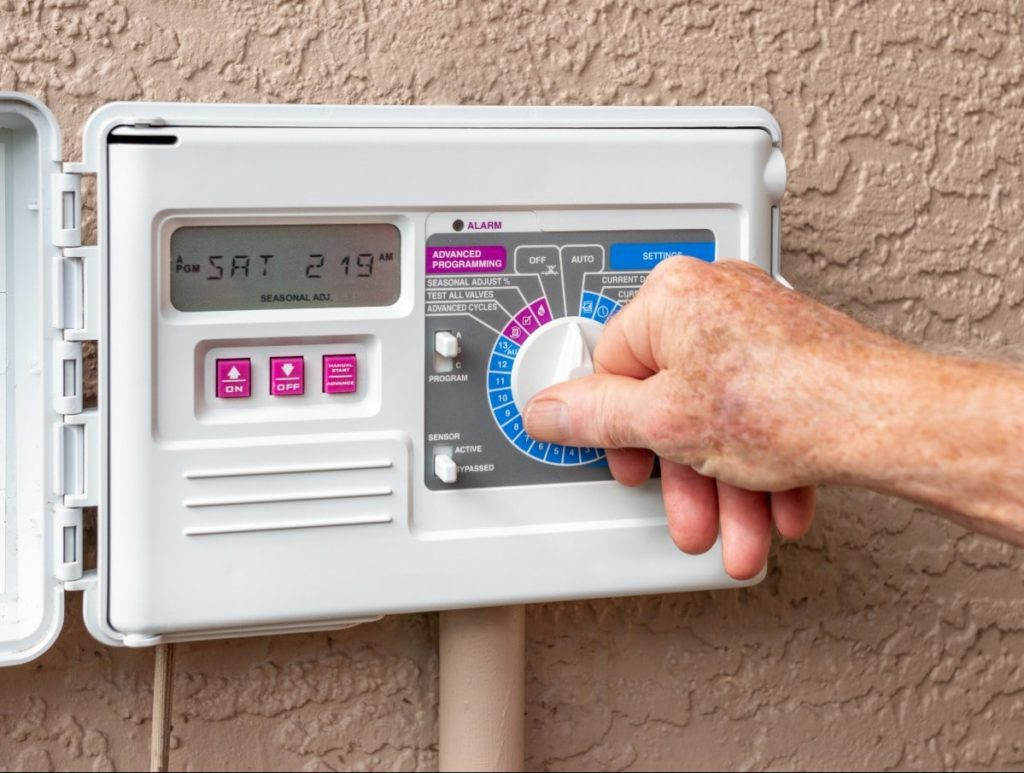 A hand is turning a nob on an control panel to set the timer on his sprinkler system in an eco-friendly home.