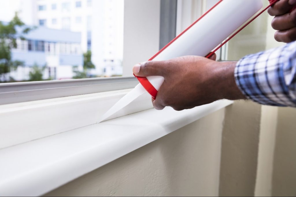 Man sealing the bottom edge of a windo with caulk in an eco-friendly home.