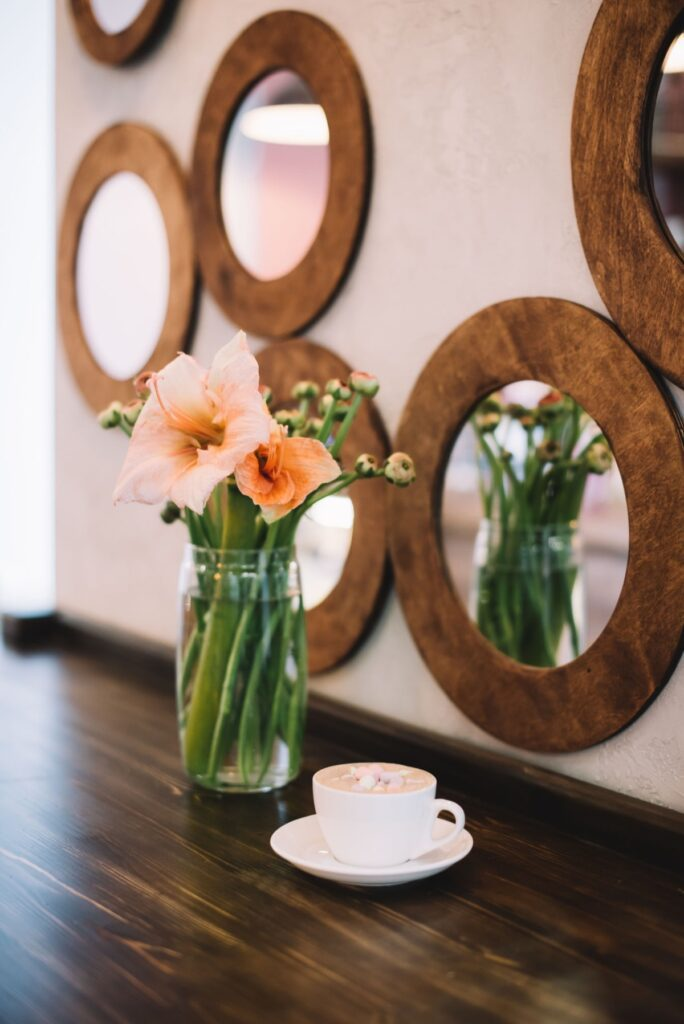 Multiple circular mirrors on the wall with a vase of flowers in front.