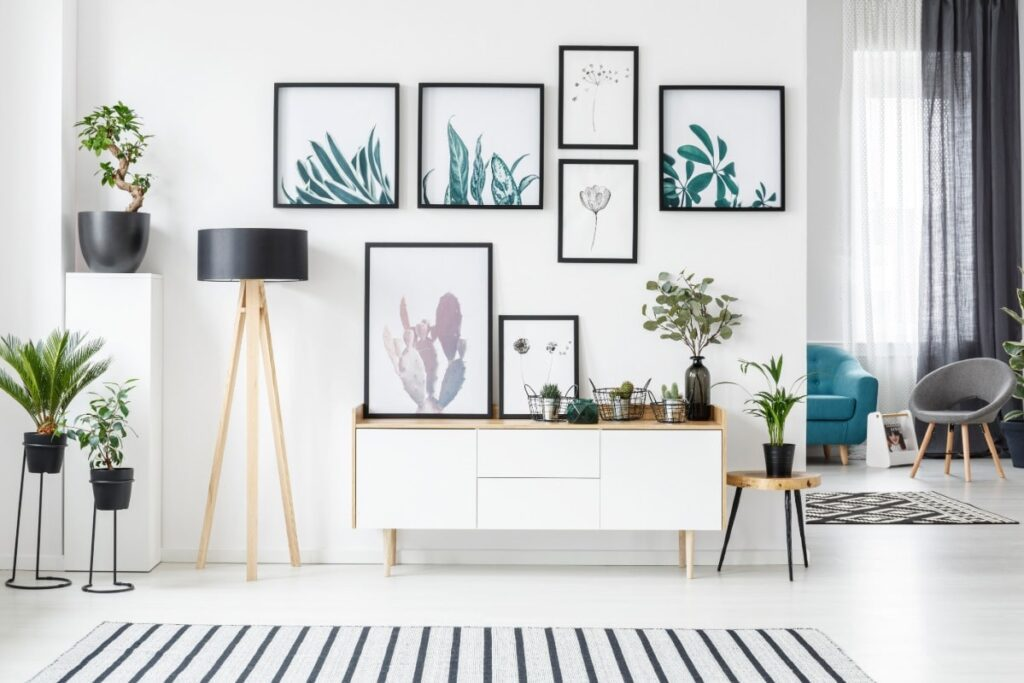 Accent wall filled with framed paintings of different plants. Dresser in front of wall topped with plant paintings and flowers. Surrounding plants are also present.