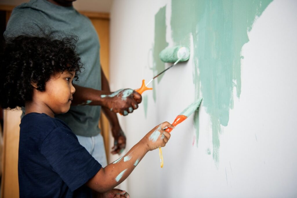 Father and son painting a wall.