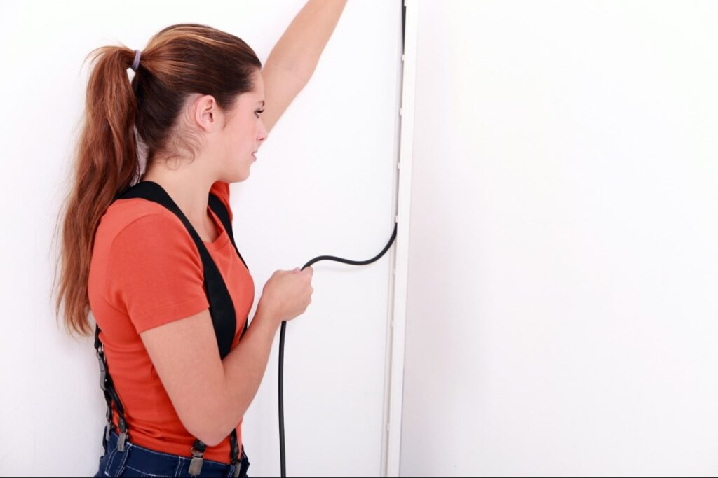 A woman hiding a wire in her home.