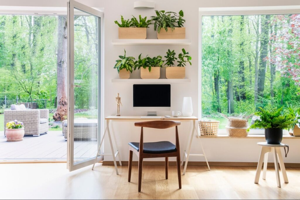 Computer desk area is located in between large window on right and large window patio doors on the left. Plants on shelf above desk area and in front of window on the right.