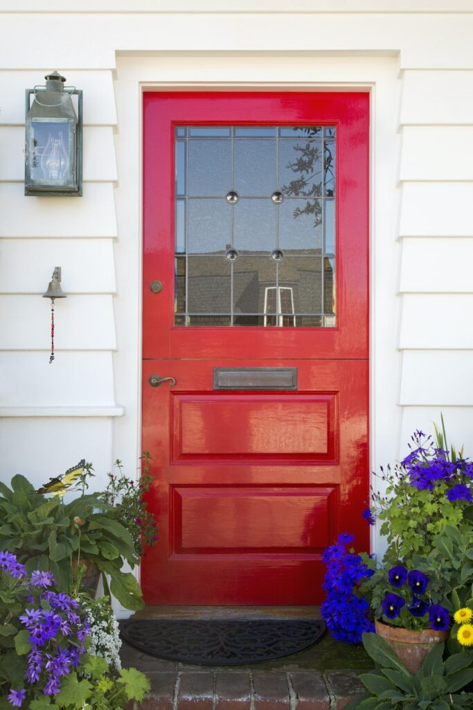 A red front door with flowers around it is one example of many curb appeal ideas.