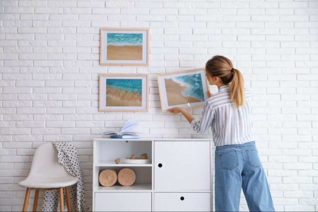 Woman hanging beach photos on the wall.