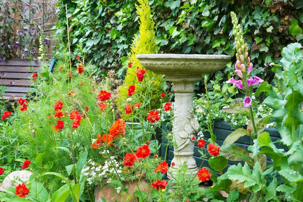 A birdbath in a front yard surrounded by flowers.