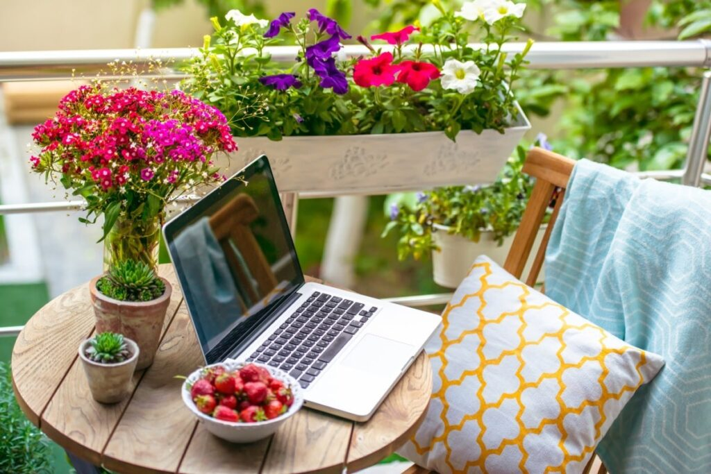 An outside area with a small circle table and chair that has a blanket and pillow on it. The table has a potted pink plant, bowl of strawberries and a laptop. Area is on a balcony next to the rail with hanging plants on it.
