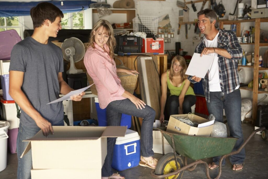 A family of four cleaning out a cluttered garage. This is a great general home repair and maintenance task to do when stuck at home.