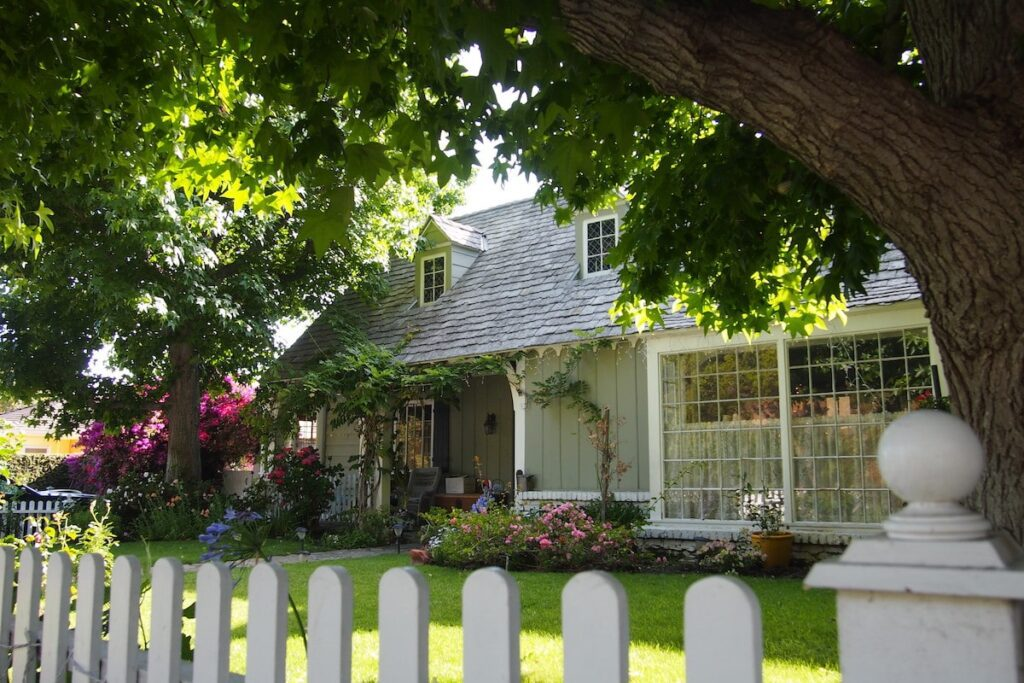 The front of a house with a few large trees, bushes and flowers.