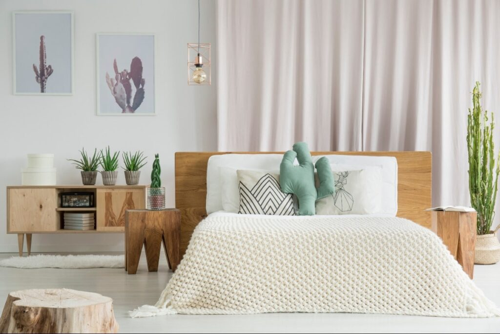 Bedroom with frame, nightstand, dresser and stool made from tree trunks and wood. Bedding includes a weaved cotton blanket and pillows.