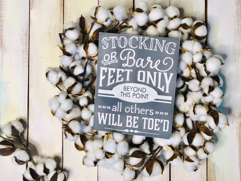 A sign creatively asking guests to remove their shoes at a front door.