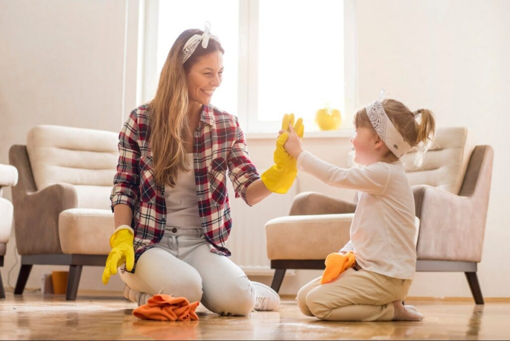 A woman and her young daughter high fiving while scrubbing their living room floor.