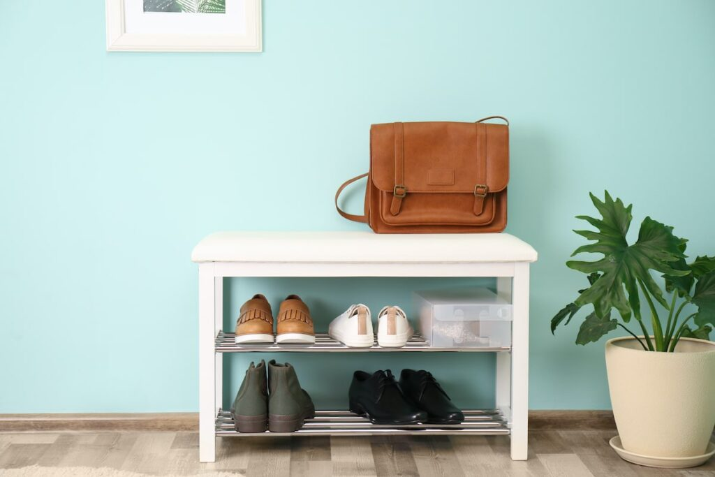 A white shoe rack with shoes on it leaning against a light blue wall.