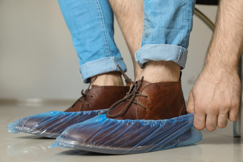 A man putting shoe covers over his shoes.
