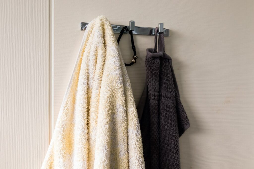 Towels hanging on a rack next to the front door.