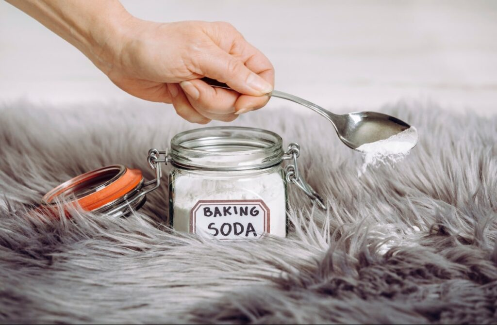 A hand is scooping out a spoonful of baking soda out of a jar onto the carpet.