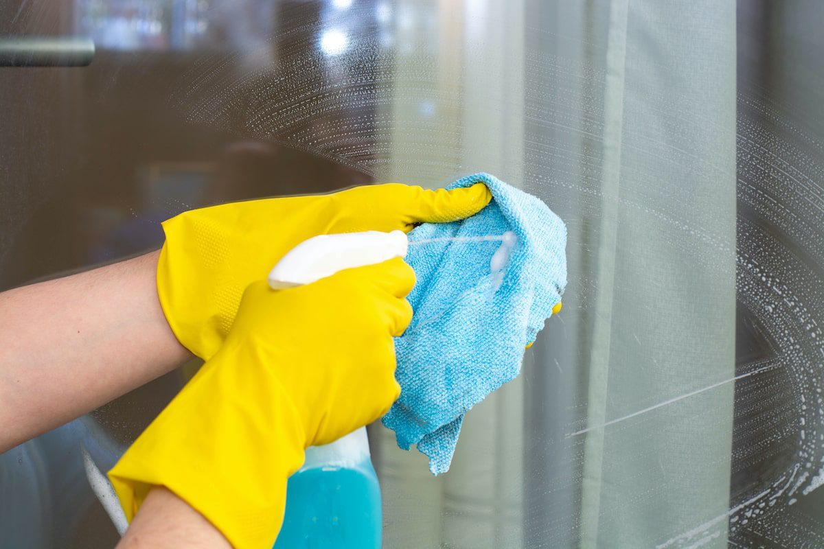 A person holding a rag and glass cleaner.