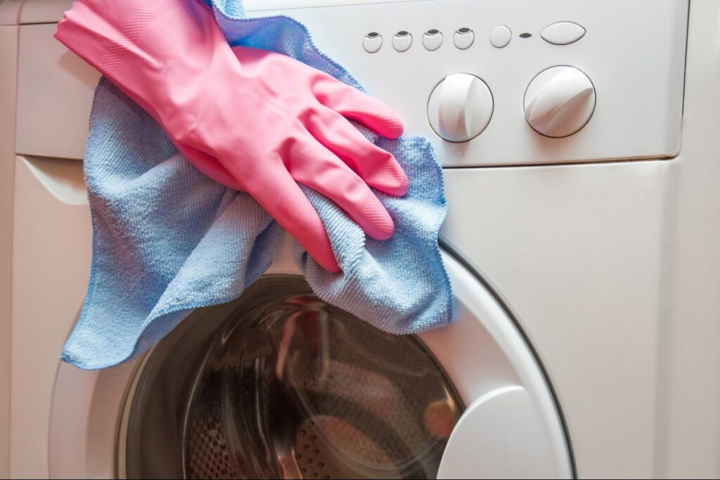 A hand, wearing disposable gloves, wiping th outside of a washing machine.