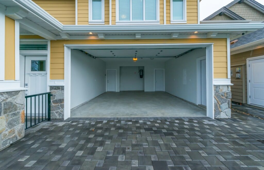 Yellow house with an open, empty garage. Garages are a great project for renovating a rental property.