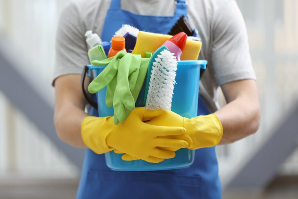 A man holding a bucket of cleaning supplies while wearing cleaning gloves.