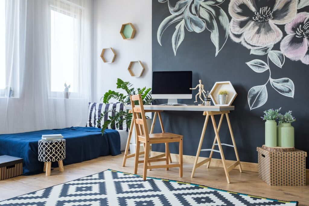 A home office with a desktop computer, wooden chair and a grey wall with flowers on it.