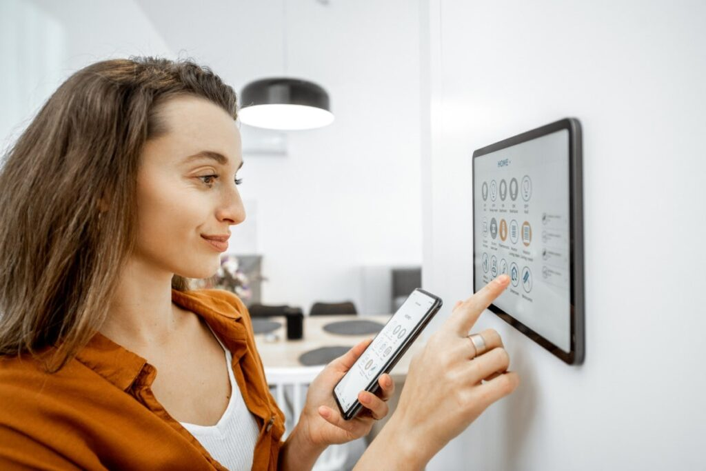 A woman is using a touchpad on her kitchen wall and her phone to control the features of her home.