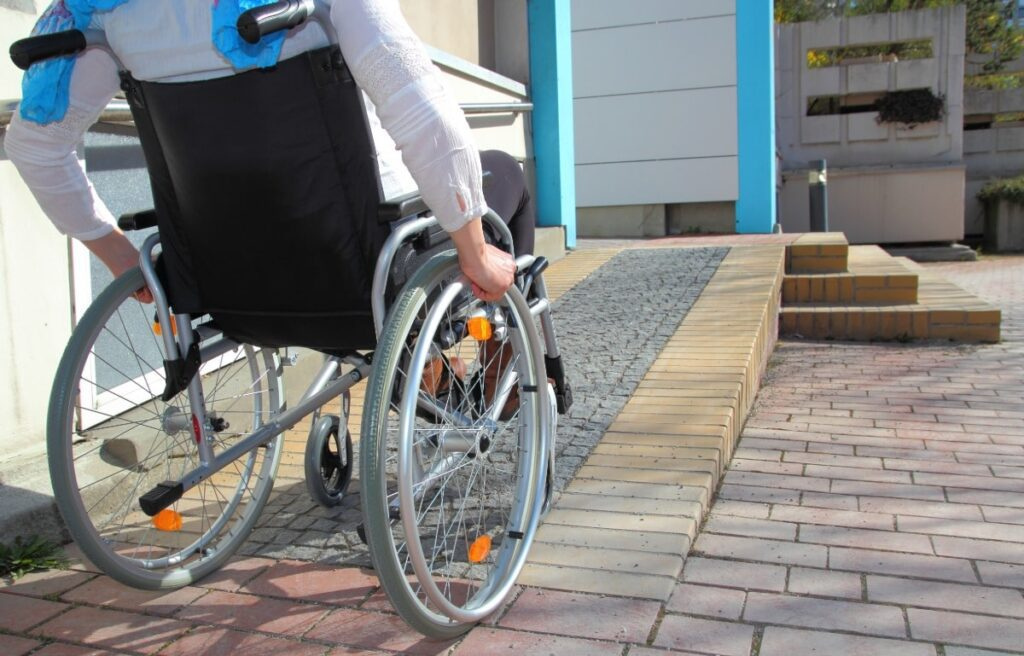 A person in a wheelchair uses a ramp to enter a rental home.