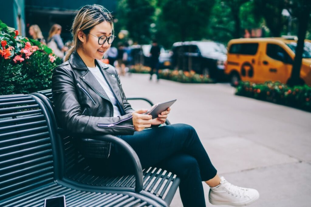 Smiling young woman sitting on a bench outdoors reading on a tablet.