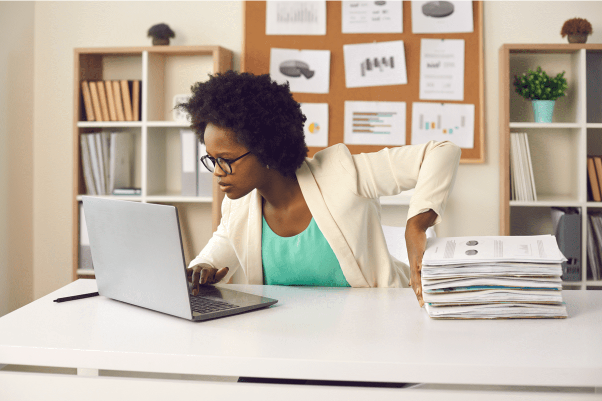 Woman with a stack of paper documents next to her and her laptop.