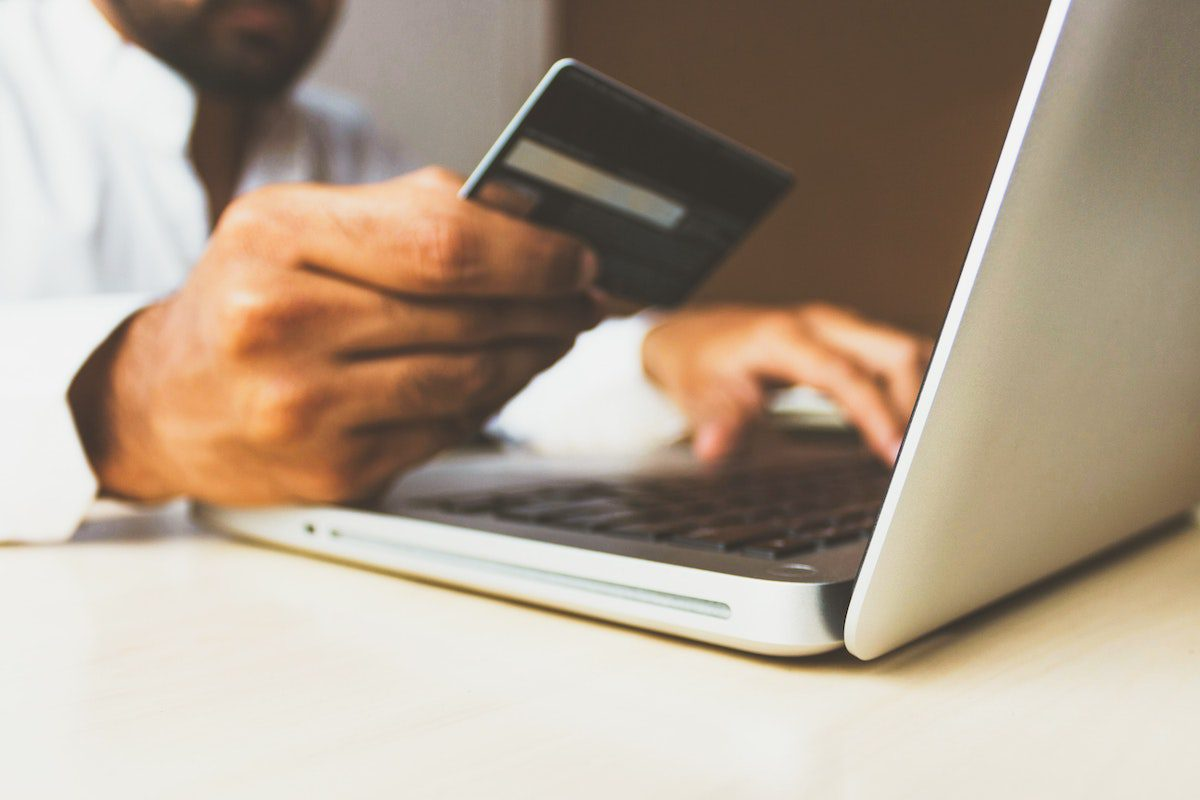 Man on a laptop using a credit card to make a payment.
