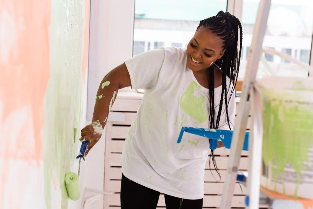 Woman painting the walls of her new rental home.