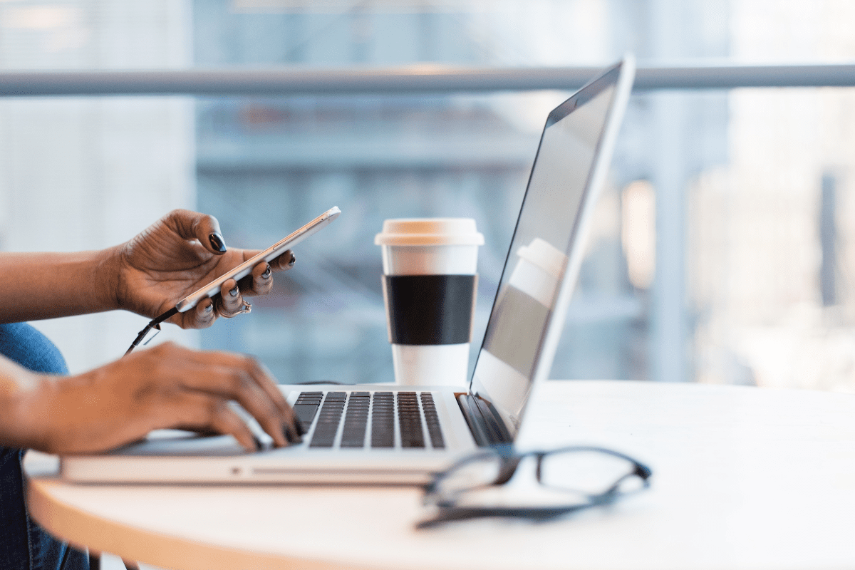 Woman on her laptop and phone with  a cup of coffee.
