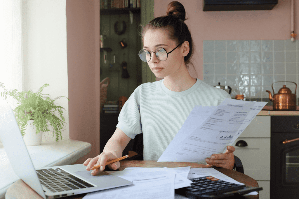 Young woman managing budget, sitting at kitchen table with open laptop, documents and calculator, using touchpad, making notes with pencil.