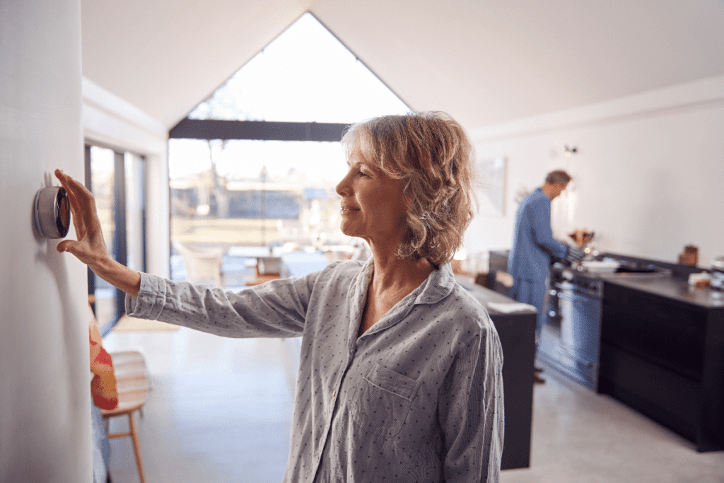 Woman adjusting wall mounted digital thermostat control at home.