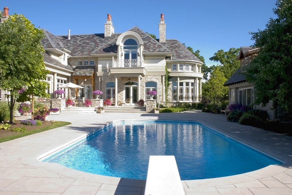 Back exterior view of mansion including pool and pool house.