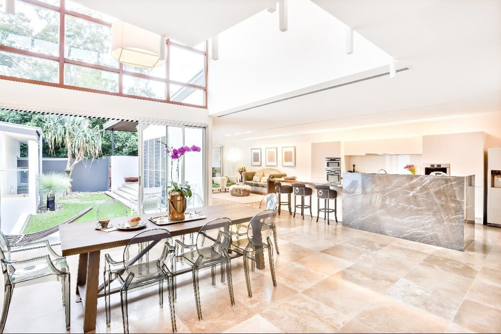 Houseouse interior and outdoor including dining and kitchen beside living room, the dining or patio area has a wooden table with plastic see through chairs on the tile floor, the house illuminated