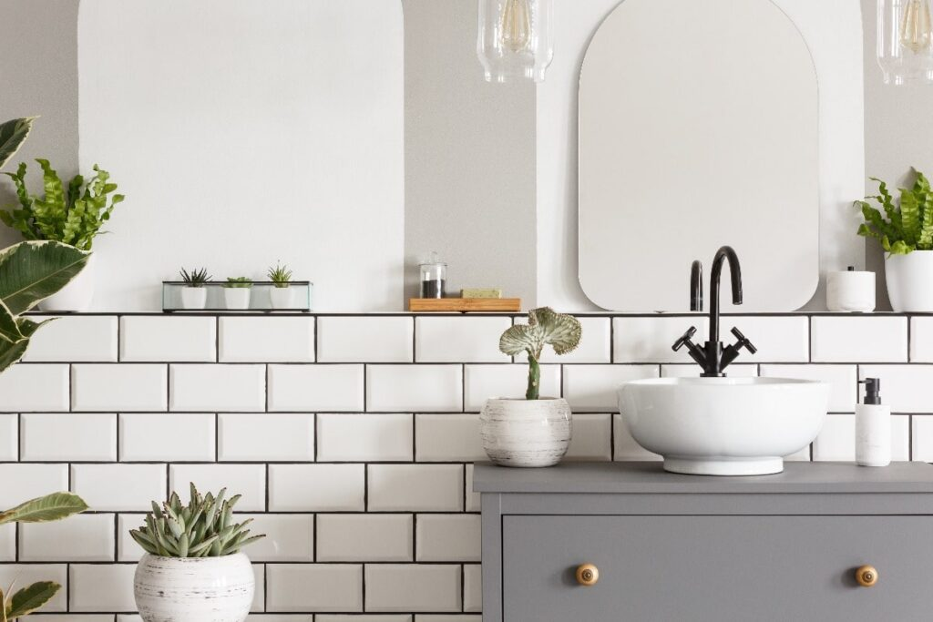 View of bathroom vanity against a white tiled, dark colored grout wall.