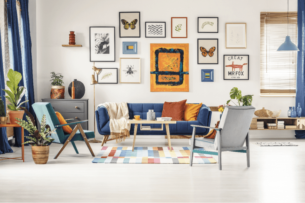 Living room with wall with multiple framed artwork created with vibrant colors.