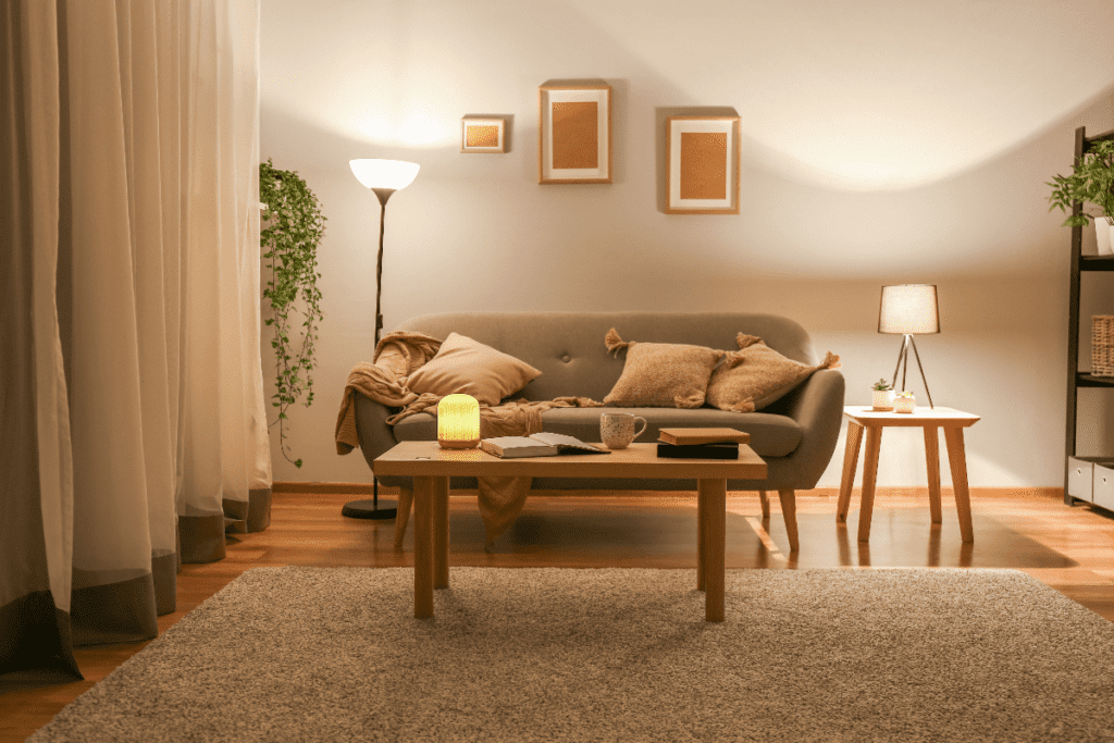 Small living room lit only with end table lamp and floor lamp, both with  white shades.
